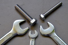 Steel wrench and fastener. S on cement background stock image