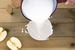 Steelpan die hete melk gieten aan plons in kom om te ontbijten royalty-vrije stock afbeeldingen