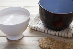 Steelpan gietende melk in kom aan ontbijt stock afbeelding