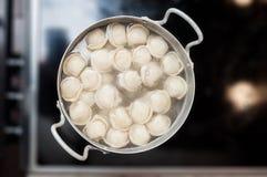 Steelpan met bollen in warm water die op kookpunt een seconde alvorens de half afgewerkte maag te vullen komen royalty-vrije stock afbeelding