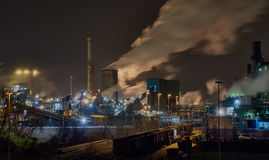 Steelplant in Duisburg, Germany, at night with lots of smoke and steam going up into the sky Royalty Free Stock Photo
