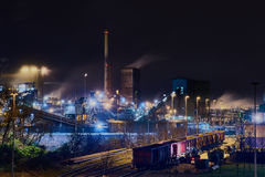 Steelplant in Duisburg, Germany, at night with a train in the front of the scene - very surreal Royalty Free Stock Photo
