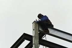 Steelworker constructing building. Steelworker welding steel beams together on construction site Stock Image