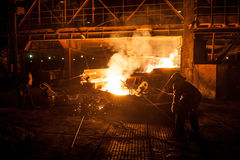 Steelworkers when pouring liquid titanium slag from arc furnace Stock Images