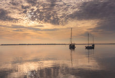 Steely Gray Morning Manteo North Carolina Waterfront. A steely calm gray glaze as the morning sun rises on the quiet east end of the Manteo, North Carolina Stock Photography