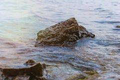 Steen dichtbij de rivier Golven die op de kustlijn in werking worden gesteld De zonsondergang van de zomer De zon` s stralen word royalty-vrije stock foto