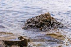 Steen dichtbij de rivier Golven op de kustlijn in werking die worden gesteld die De zonsondergang van de zomer De zon` s stralen  stock foto's