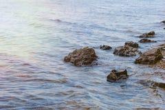Steen dichtbij de rivier Golven op de kustlijn in werking die worden gesteld die De zonsondergang van de zomer De zon` s stralen  stock foto