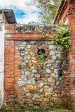 Steen en bakstenen muur tussen aan abandondstructuren Stock Fotografie