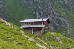 Steen en houten chalet op de bergketen stock foto