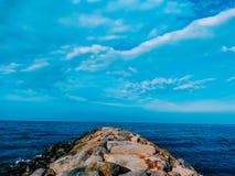 Steen in hemel en overzeese horizon stock afbeeldingen