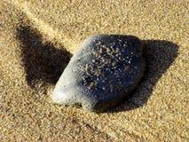 Steen over zand met schaduw royalty-vrije stock afbeelding