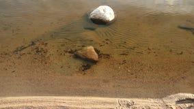Steen in water op kust van meer stock footage