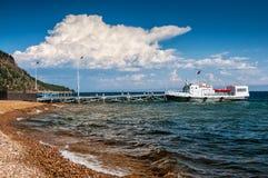 Steenachtig kust en schip bij de pijler in zonnige dag en wolk royalty-vrije stock afbeelding