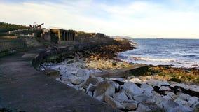 Steenachtige kust van het overzees met betonconstructies op de kust Royalty-vrije Stock Foto's