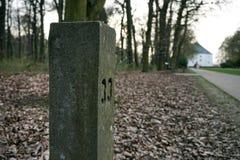 Steenachtige mijlpaal naast de touristy weg Stock Afbeeldingen
