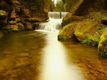 Steenachtige waterkering op kleine bergrivier De stroom stroomt over vierkante blokken en maakt melkachtig water royalty-vrije stock foto's