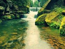 Steenachtige waterkering op kleine bergrivier De stroom stroomt over vierkante blokken en maakt melkachtig water royalty-vrije stock afbeelding