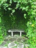 Steenbank in groene de zomertuin stock afbeelding