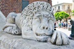 Steenbeeldhouwwerk van een leeuw die voor de ingang aan een oud gebouw liggen royalty-vrije stock foto