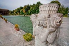 Steenbeeldhouwwerk van vrouw en leeuwen dichtbij de pool van Perzisch paleis Hasht Behesht in Iran Stock Foto