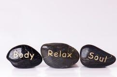 Steenbehandeling Zwarte die stenen op een witte achtergrond masseren Hete stenen saldo zen als concepten Basaltstenen Stock Foto's