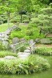 Steenbrug met houten kaders, watervijver, grassen Stock Afbeelding