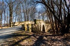 Steenbrug over een kleine rivier Stock Foto