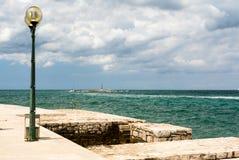Steendijk, uitstekende lantaarn en kleine vuurtoren op achtergrond Royalty-vrije Stock Afbeeldingen
