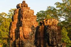 Steengezichten in Bayon, de tempel van Angkor Thom, het selectieve licht van de nadrukzonsondergang Het concept van de boeddhisme stock afbeelding