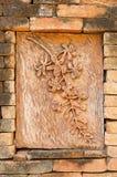 Steengravure van bloemen op de achtergrond van de bakstenen muurtextuur stock fotografie