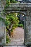 Steeningang die tot een formele tuin leidt Stock Foto's