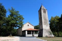 Steenklokketoren met kerk op achtergrond stock afbeeldingen