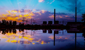 Steenkoolelektrische centrale bij zonsondergang en bezinning in water stock foto's