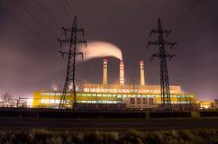 Steenkoolelektrische centrale met schoorstenen en machtslijn bij nacht Stock Foto's