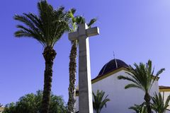 Steenkruis en de koepel van de kerk tegen de achtergrond van blauwe hemel en palmen Symbool van geloof, godsdienst, Christendom royalty-vrije stock afbeelding