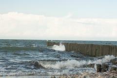 Steenkust, overzeese golven die tegen de golfbrekers, achtergrond, blur2 slaan stock foto's