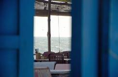 Steenlijsten met stoelen in een koffie onder een luifel op de kust die de Vreedzame Oceaan overzien stock foto