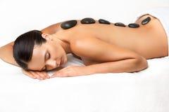 Steenmassage. Beautiful Woman Getting Spa Hete Stenenmassage binnen stock foto