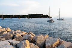 Steenpijler bij zonsondergang In de overzeese varende boot met een mast en een zeil Tegen de achtergrond van een eiland Stock Foto's