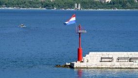 Steenpijler met vuurtoren en vliegende vlag in daglicht, motorboot op achtergrond stock video