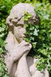 Steenstandbeeld van vrouw dat door klimop wordt overwoekerd stock foto