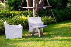 Steenstoel en lijst in de tuin, de Struiken en de groene gazons royalty-vrije stock afbeelding