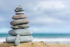 Steentoren op een strand als achtergrond met exemplaarruimte stock fotografie