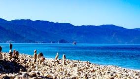 Steentorens op de kust van het strand met een overzees met intens blauw water, een boot en bergen op de achtergrond stock fotografie