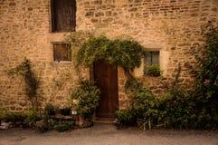 Steenvoorgevel met Bloemen in de Stegen van het Kleine Middeleeuwse Dorp van Bruniquel stock foto