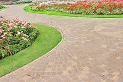 Steenwegen in aardtuin met kleurrijke sierbloemenachtergrond stock foto