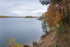 On the steep Bank. On the steep Bank of a large river. Autumn colors painted in bright colors shore Stock Photography