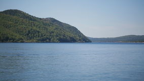 Steep bank of sea or lake with thick forest on a sunny day and blue sky. stock video footage