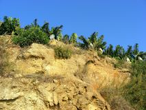 Steep cliff. Sheer cliff of layered rocks on the mountain backdrop of blue sky Stock Images
